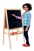 Happy schoolchild writing on blackboard — Stock Photo
