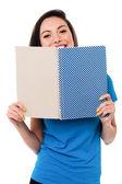 Giovane ragazza nascondendo il viso con il notebook — Foto Stock