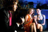 Flirtatious young girls staring at handsome guy — Stock Photo