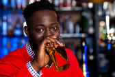 African guy drinking beer, blur background — Stock Photo