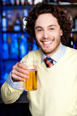 Positive young man holding a glass of beer — Stock Photo