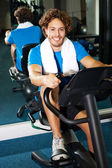 Handsome man at the gym doing static cycling — Stock Photo