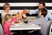 Family toasting smoothies in restaurant — Stock fotografie