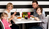 Family eating lunch together in restaurant — Stockfoto