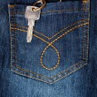 Key hanging out of back pocket of a jeans — Stock Photo