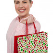 Cheerful blonde girl holding shopping bag — Stock Photo