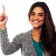 Casual smiling girl pointing upwards — Stock Photo