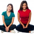 Young girls sitting on the floor, studio shot — Stock Photo