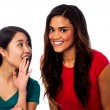 Two pretty young girls gossiping — Stock Photo
