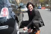 Businessman repairing car roadside — Stock Photo