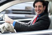 Cheerful man driving his new luxurious car — Stock Photo