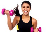 Excited asian girl lifting dumbbells — Stock Photo
