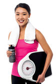 Fit girl holding weight scale and sipper bottle — Stock Photo