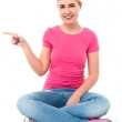 Pretty teen girl pointing at something — Stock Photo #27658065