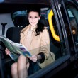 Stock Photo: Female passenger reading newspaper inside taxi