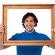 Smiling guy looking through picture frame — Stock Photo