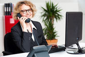Happy front desk lady attending clients call — Stock Photo
