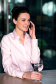 Woman communicating over cellphone to client — Stock Photo