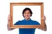 Glimlachende man op zoek via afbeeldingsframe — Stockfoto