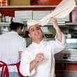 Chef throwing up thin base dough — Stock Photo