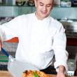 Chef placing pizza, ready to be served. — Stock Photo