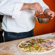 Cropped image of a chef preparing pizza — Stock Photo