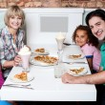 Cheerful family of four enjoying dinner — Stock Photo #29204075