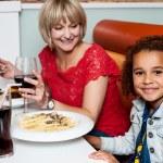 Little girl enjoying dinner with her mom — Stock Photo #29204091