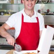 Chef holding pizza cuter, ready to cut. — Stock Photo #29204097