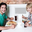 Young smiling couple enjoying lunch — Stock Photo
