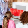 Stock Photo: Mshowing daughters how to order pizzonline