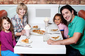 Cheerful family of four enjoying dinner — Stock Photo
