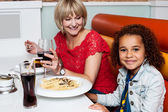 Little girl enjoying dinner with her mom — Stock Photo