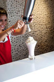 Attractive girl pouring shake in glass — Stock Photo