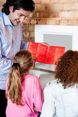 Man showing daughters how to order pizza online — Stock Photo