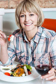 Woman relishing her meal with red wine — Stock Photo