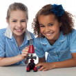 Joyous young school girls with microscope — Stockfoto