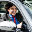 Handsome businessman driving a luxurious car — Stock Photo