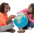 Young girls locating countries on globe — Stock Photo