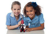 Joyous young school girls with microscope — Stock Photo