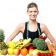 Slim fit girl with fresh fruits and vegetables — Stock Photo