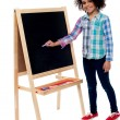 Charming young girl writing on blackboard — Stock Photo