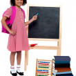Pretty schoolgirl pointing at chalkboard — Stock Photo
