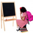 Thoughtful kid sitting in front of blackboard — Stock Photo #29710647