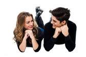 Young couple lying on the studio floor — Stock Photo