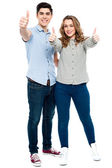 Attractive couple showing thumbs up — Stock Photo