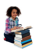 Cute kid reading book with magnifying glass — Stock Photo