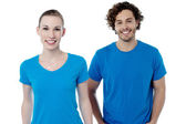 Couple in blue t-shirts. Isolated over white. — Stock Photo