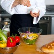 Chef sprinkling salt on vegetables — Stock Photo