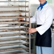 Chef moving tray rack towards corner — Stock Photo